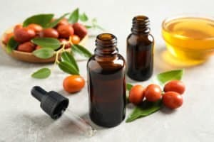 Glass bottle with jojoba oil and seeds
